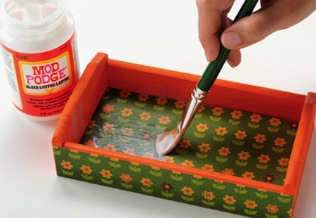 Painting a top coat of Mod Podge on the inside of a tray