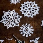A group of homemade paper snowflakes on a counter with a pair of scissors