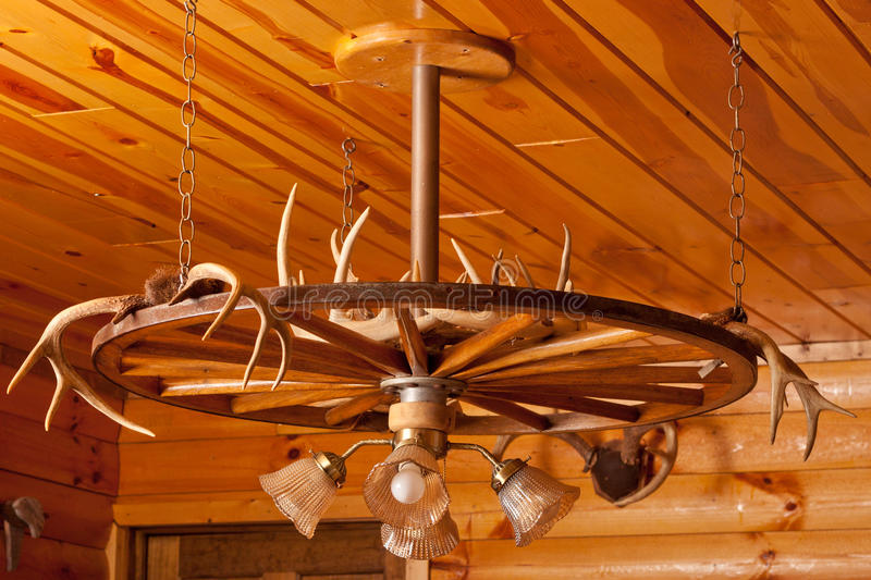 Antler Chandelier. With light fixture hanging from the wooden ceiling of a log cabin stock images