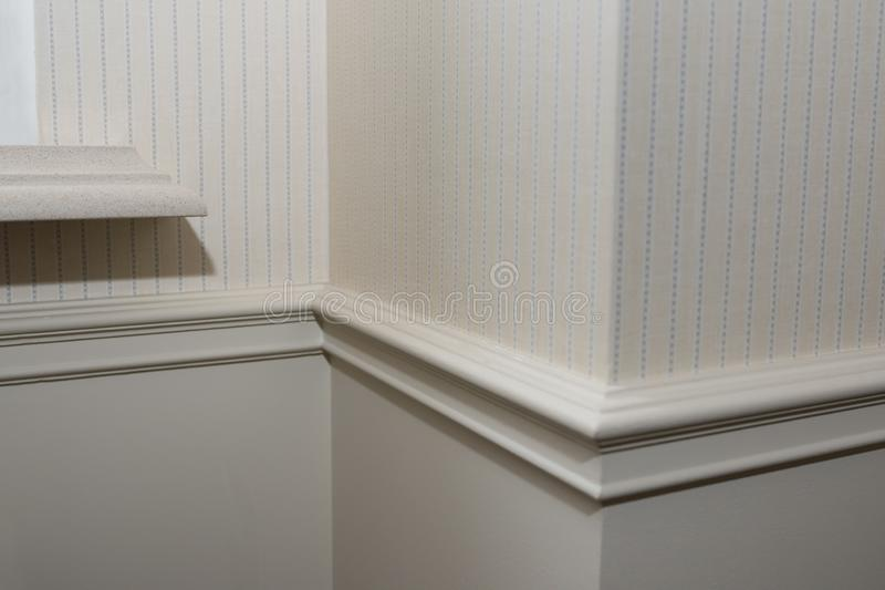 Ceiling moldings in the interior, detail of a angular wall skirting. stock images