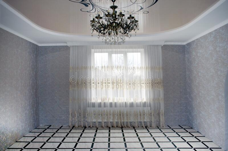 Classic empty interior with a light wall, stone tiles on the floor, window and curtain, decor, ceiling, skirting and a large. Beautiful chandelier stock photos