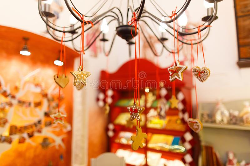 The close-up view of the christmas cookies hanging on the chandelier at the blurred background of the shop. The close-up view of the christmas cookies hanging royalty free stock photos