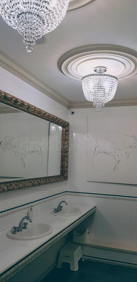 Elegant bathroom with white interior and elegant chandelier royalty free stock images