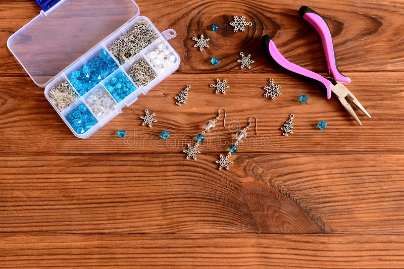 Handmade female chandelier earrings. Beautiful earrings made of blue and white beads and metal snowflakes. Pliers, box of craft materials on a wooden table stock image