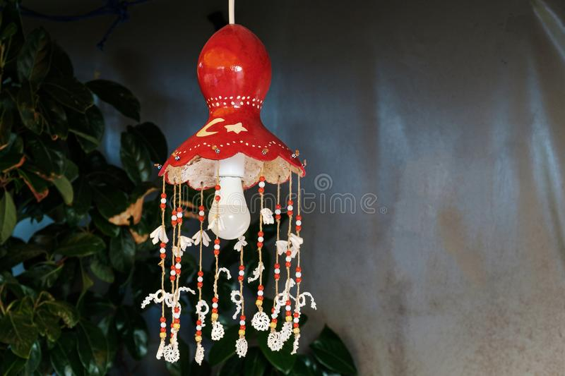 Homemade lamp with a bulb in the style of the Turkish flag and colors of the country. Red chandelier on a wire with handmade decorations royalty free stock images