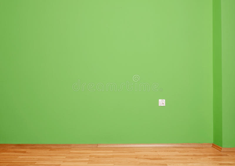 Interior room with wooden floor and wall in green with an electrical contact in the wall and wooden skirting. Interior room with wooden floor and wall in green stock images
