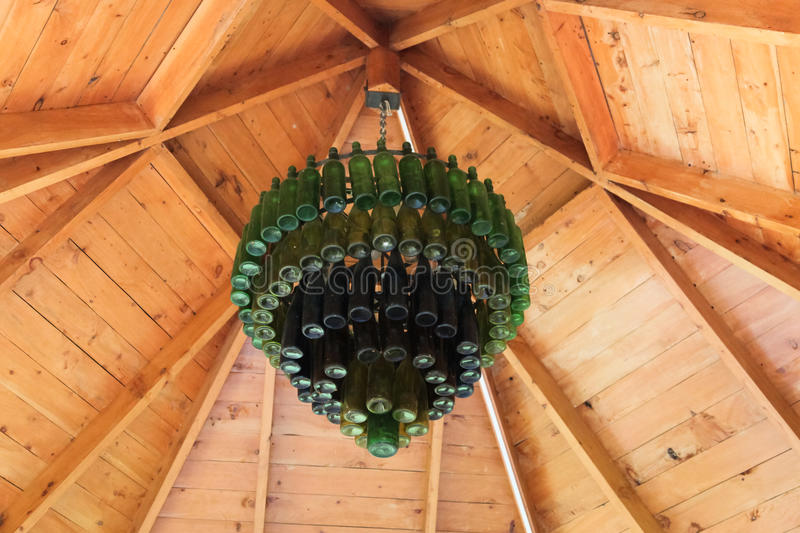 Old Bottle Chandelier. A chandelier made from old bottles in green and blue hang from the inside of a wooden gazebo royalty free stock photos