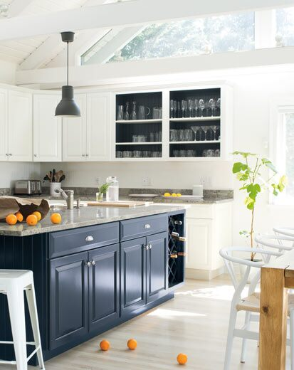 A bright, airy kitchen with blue island and white walls and cabinets