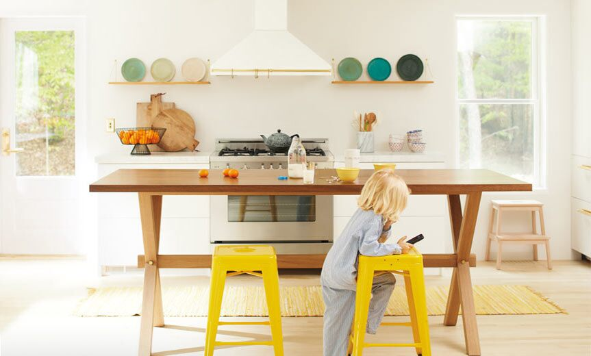 An open, inviting kitchen with neutral walls and bright yellow chairs