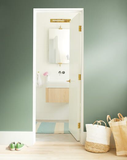 A dark green wall leads to a bright, neutral bathroom