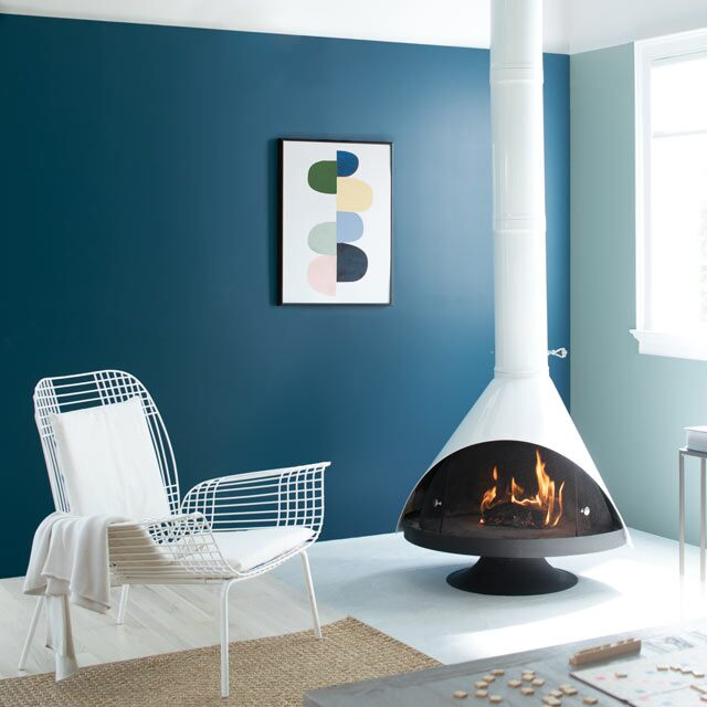 A cozy living room complete with a retro fireplace accompanied by blue painted walls