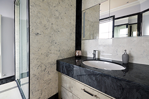 Gloucester marble vanity top with an undermounted sink and wall panels in arabesque